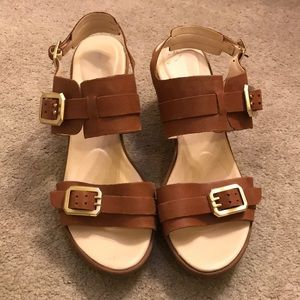 Brown leather Rockport sandals with gold detail.